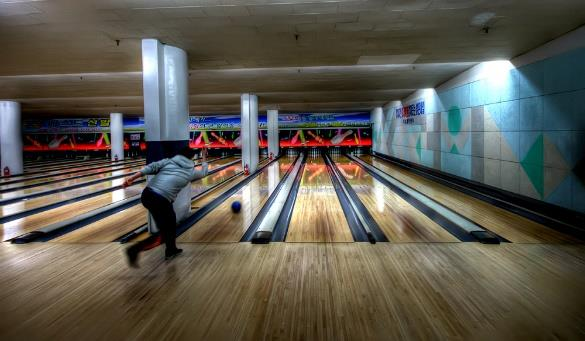 man releasing a ball while bowling at a bowling alley